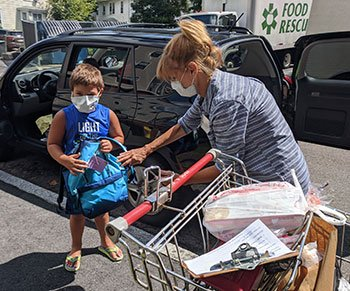 Interfaith Social Services volunteer Marzie Gans, of Quincy, (right) gives a backpack to Joshua Hashorva, of Braintree (left). Volunteers distributed more than 600 backpacks to the children of Interfaith's food pantry clients in August.